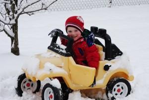 Kind mit Tretauto im Schnee